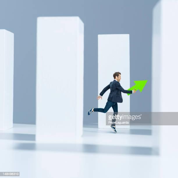 mann läuft mit grüner pfeil in modernem ambiente - advertising column stock-fotos und bilder