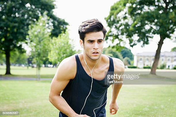 man running with headphones in park