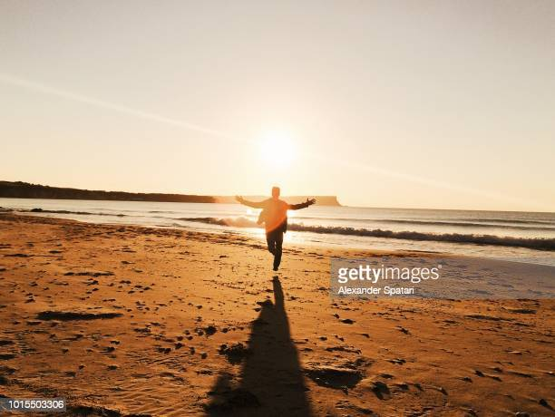 Man running with his arms spread at the beach during sunset