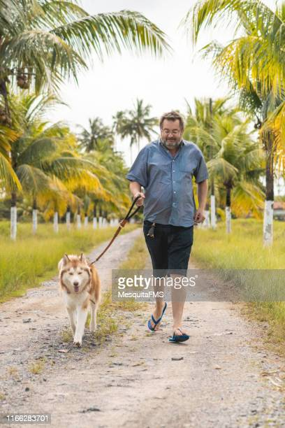 man running with his best friend - hairy old man stock pictures, royalty-free photos & images