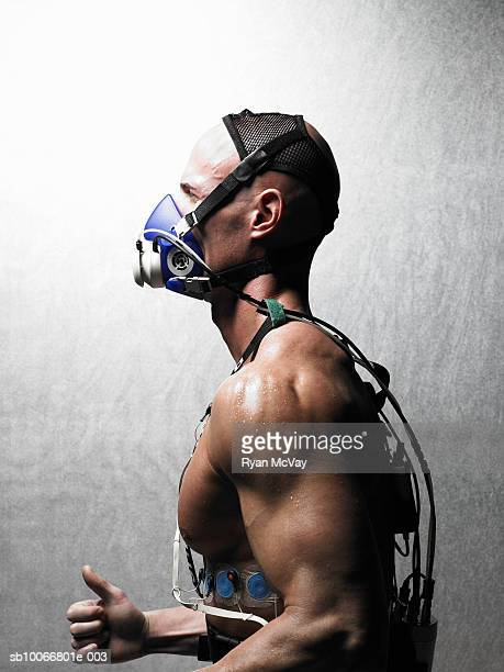 Man running with oxygen mask and EKG, close-up, side view
