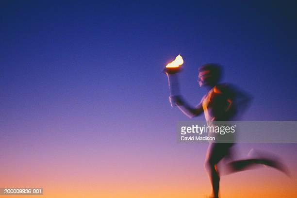 man running with torch at sunset (defocused) - 聖火トーチ ストックフォトと画像