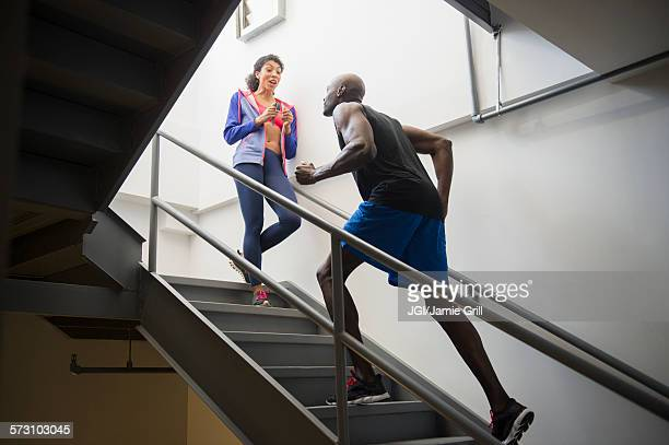 Man running with trainer on staircase