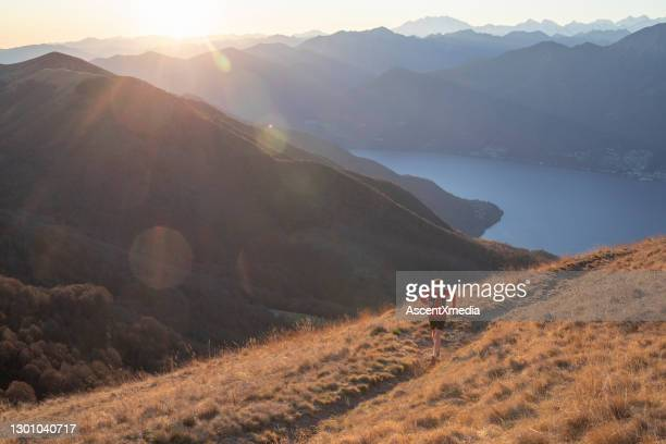 man runs above mountains and lake at sunrise - forward athlete stock pictures, royalty-free photos & images