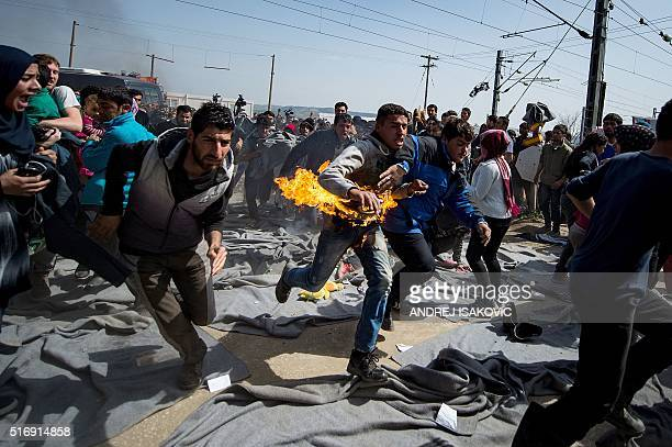 TOPSHOT A man runs after he tried to put himself on fire during a protest at a makeshift camp at the GreekMacedonian border near the village of...