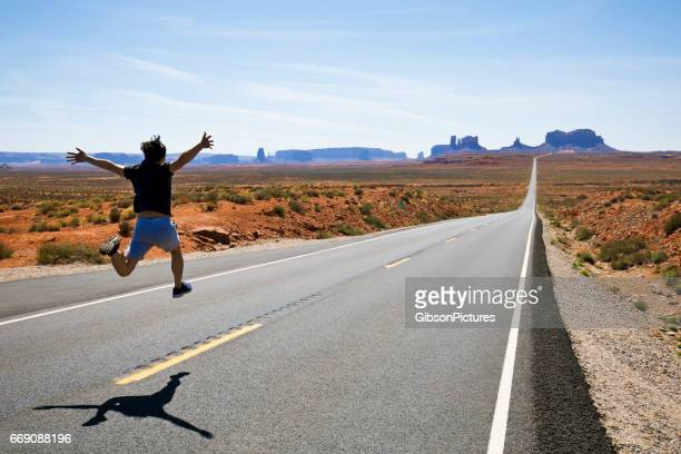 A man runs and jumps along a section of Highway 163 in Monument Valley, Utah, USA.