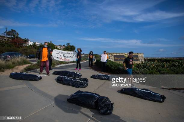 A man runs around symbolic homemade bodybags that it were left by activists in front of the Trump National Golf Club on April 18 2020 in Rancho Palos...