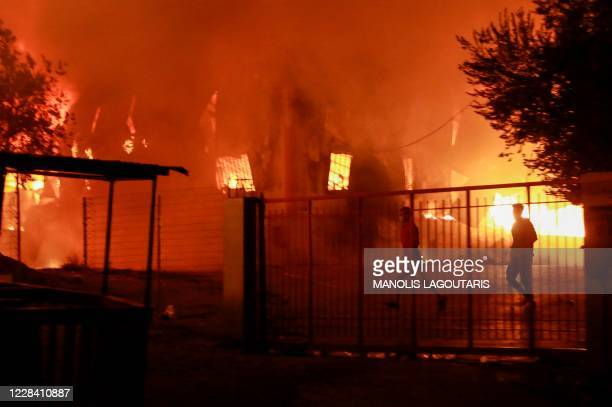 Man runs as a fire burns inside the Moria migrant camp on the island of Lesbos on September 9, 2020.