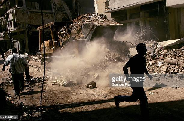 Man runs by the scene of a building collapse the morning after an Israeli attack August 8, 2006 in Beirut, Lebanon. The evening target was the...