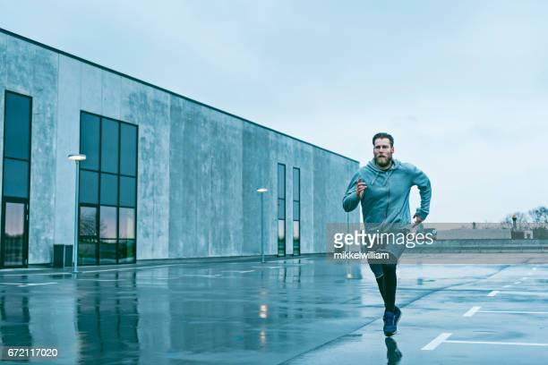 Man runs fast outside and the sky is grey