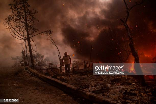 Man runs from flames after a major fire broke out in the Moria migrants camp on the Greek Aegean island of Lesbos, on September 9, 2020. - Thousands...