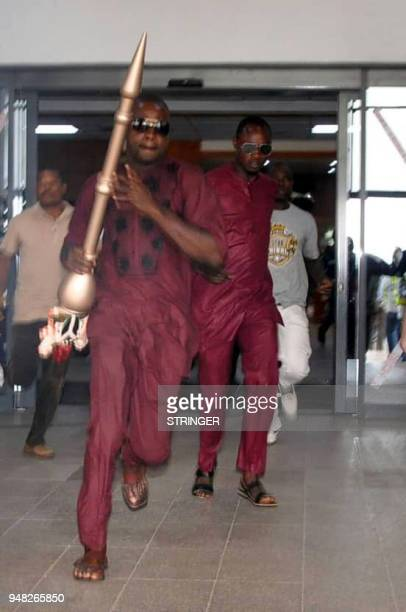 A man runs holding mace the symbol of authority of the Upper Legislative Chamber seized at the chamber in Abuja on April 18 2018 The ceremonial mace...