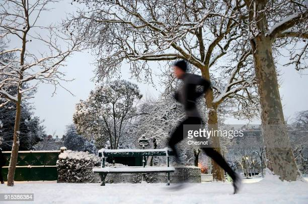 A man runs in the early morning in the Champs de Mars garden covered by snow near the Eiffel Tower on February 7 2018 in Paris France After...