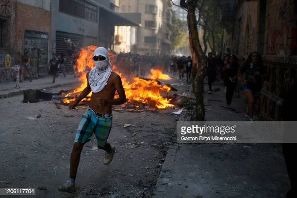 A man runs next to a burning barricade during protests as part of the International Women's Day at Plaza Baquedano on March 8 2020 in Santiago Chile
