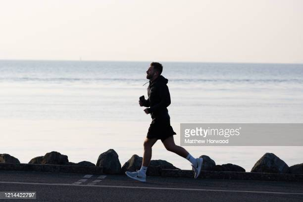 A man runs on Cardiff Bay barrage on March 24 2020 in Cardiff United Kingdom British Prime Minister Boris Johnson announced strict lockdown measures...