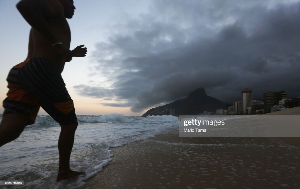 A man runs on Ipanema Beach on October 26, 2013 in Rio de Janeiro, Brazil. Brazil is gearing up to host the 2014 FIFA World Cup and Rio 2016 Olympic Games.