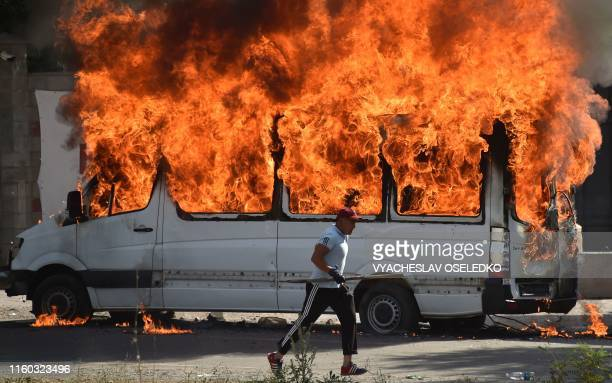 Man runs past a burning bus during clashes between supporters of Kyrgyzstan's former president and law enforcement in the village of Koy-Tash, some...