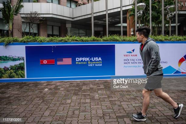 A man runs past a DPRKUSA summit banner outside the Melia Hotel where a number of North Korean delegates are staying for the forthcoming DPRKUSA...