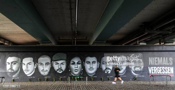 Man runs past a mural with portraits of victims of the Hanau shootings on February 19, 2020 under a bridge in Frankfurt am Main, western Germany, on...