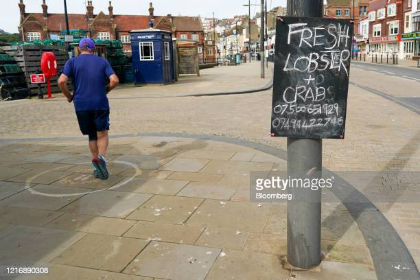 A man runs past a sign advertising fresh lobster and crab in the harbour in Scarborough UK on Tuesday June 2 2020 The threat of a nodeal Brexit is...