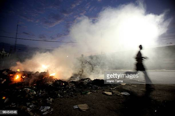 Man runs past as trash is burned in the street due to a lack of garbage collection February 5, 2010 in Port-au-Prince, Haiti. The death toll from the...