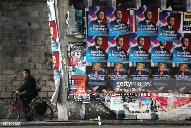 A man runs past posters of presidential candidates Emmanuel Macron and Marine Le Pen whose faces have been changed to that of US President Donald...
