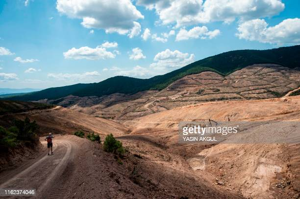 A man runs past the gold mine site project of Canadabased Alamos Gold in a deforestated area in Turkey's northwestern province of Canakkale near the...
