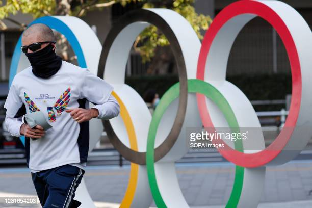 Man runs past the Olympic symbols of the five interlaced rings seen near the National Stadium in Tokyo. The government has decided to exclude...