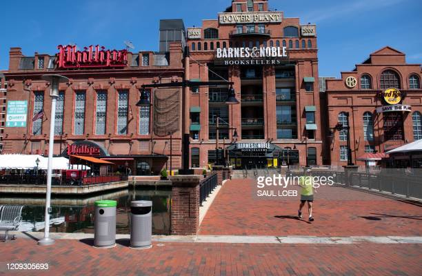 Man runs through a normally busy area of Baltimore's Inner Harbor in Maryland, April 6 as the state continues a stay-at-home order due to the...