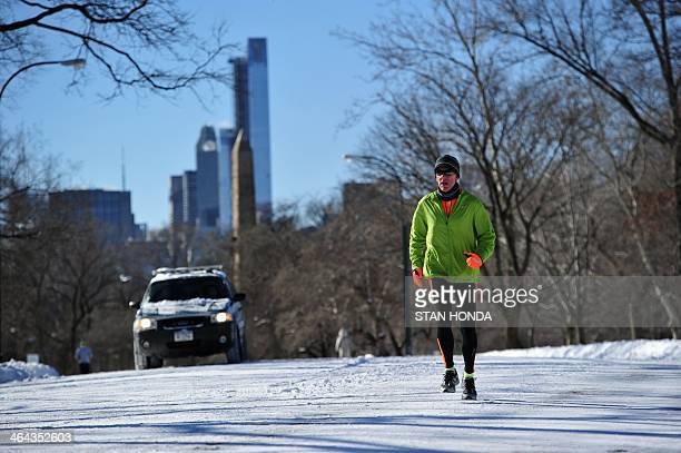 A man runs through Central Park in frigid temperatures January 22 2014 in New York The northeastern US shivered amid heavy snowfall and far below...