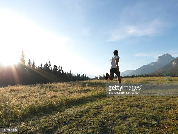 man runs through mountain meadow, sunrise - running shorts stock pictures, royalty-free photos & images