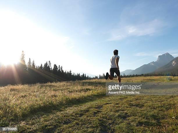 man runs through mountain meadow, sunrise - ランニングショートパンツ ストックフォトと画像