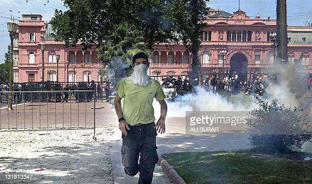 Man runs to avoid the tear gas in Buenos Aires, Argentina 20 December 2001. Un manifestante se aleja de los gases lacrimógenos lanzados por la...