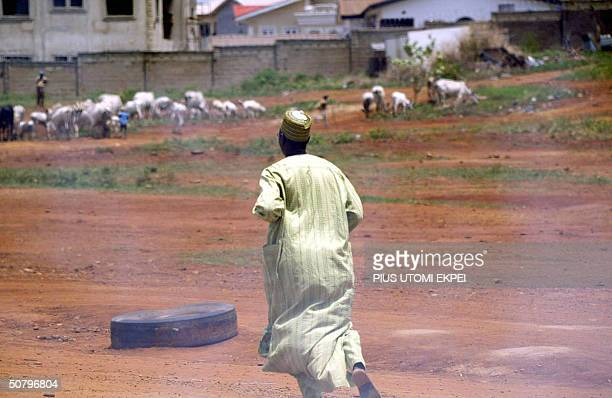 Man runs to safety as police fire tear gas at opposition demonstrators during an anti-government rally in Abuja, 03 May 2004. Nigerian riot police...