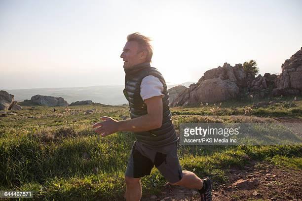Man runs up mountain road, sea below