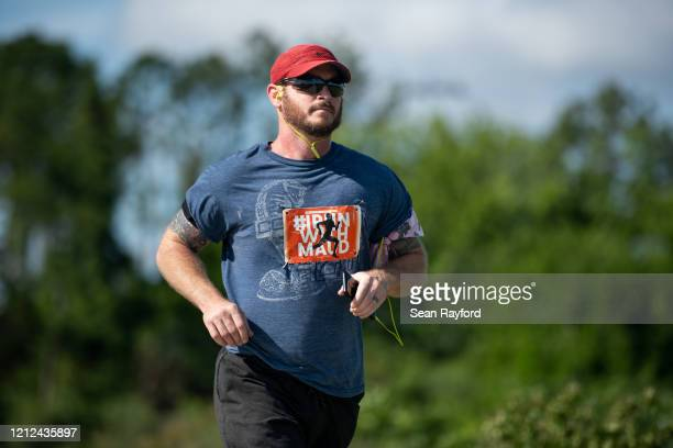 A man runs while honoring the life of Ahmaud Arbery on May 9 2020 in Brunswick Georgia Arbery was shot and killed while jogging in the Satilla Shores...