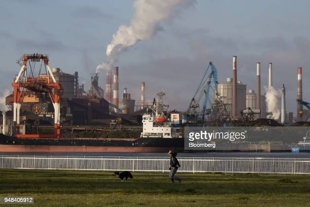 A man runs with a dog in front of the Nippon Steel Sumitomo Metal Corp plant at a park in Kamisu Ibaraki Japan on Wednesday April 18 2018...