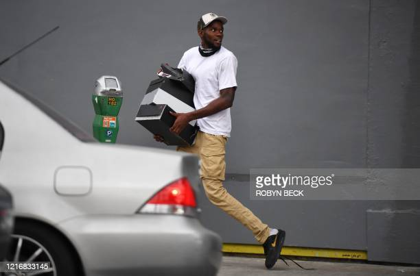 A man runs with boxes of shoes after looters broke into a shoe store in Hollywood California June 1 after a demonstration over the death of George...