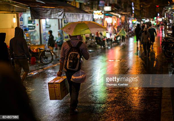 A man runs with his shopping and a broken umbrella through a shopping street in Hanoi in the evening on October 30 2016 in Hanoi Vietnam