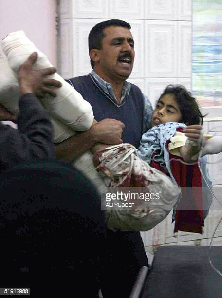 A man rushes with an injured girl in the hospital in the town of Baquba 60 kms northeast of Baghdad 04 January 2005 after a rocket slammed into their...