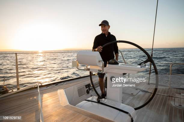 a man sailing a beautiful yacht on the open ocean. - ricchezza foto e immagini stock