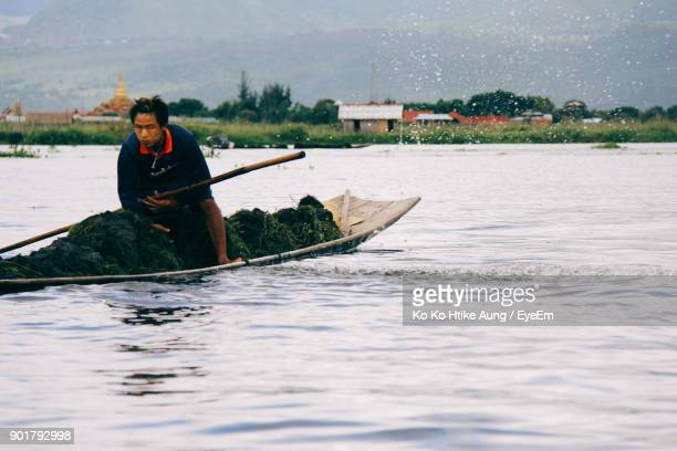 man sailing boat in lake against sky - ko ko htike aung stock pictures, royalty-free photos & images