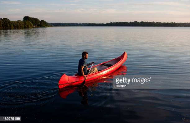 man sailing canoe on lake