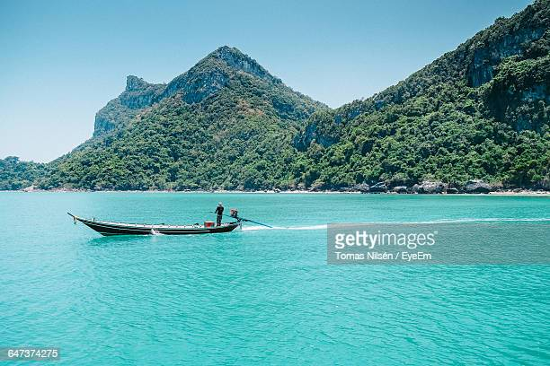 Man Sailing On Boat By Tree Mountains In Ko Samui
