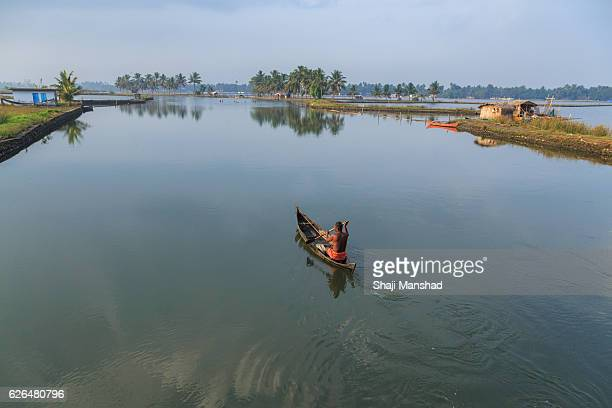 Man sailing through backwaters in a village in Kerala