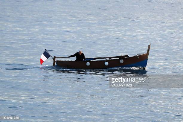 A man sails on a traditional 'pointu' boat off the Promenade des Anglais in the French riviera city of Nice on January 12 2018 / AFP PHOTO / VALERY...