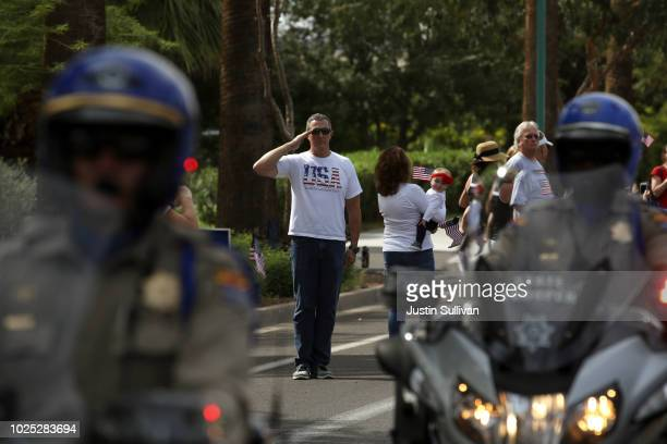 A man salutes as a hearse carrying the casket of US Sen John McCain is escorted by Arizona State Troopers to a memorial service at the North Phoenix...