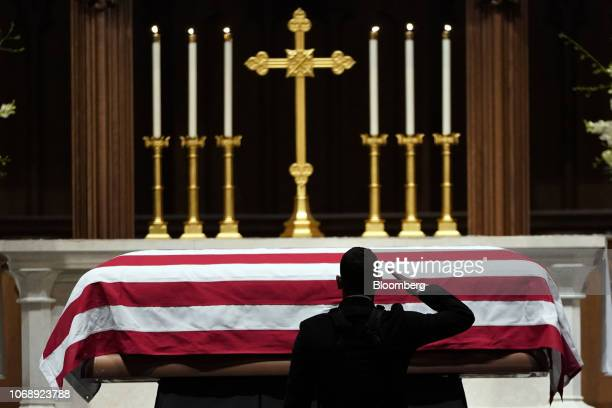 A man salutes as the flagdraped casket of former US President George HW Bush sits on the repose at St Martin's Episcopal Church in Houston Texas US...