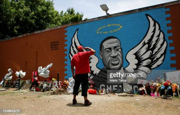 A man salutes at a mural dedicated to George Floyd across the street from the Cuney Homes housing project in Houston's Third Ward where Floyd grew up...