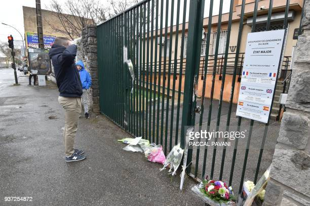 A man salutes next to flowers laid in front of the Gendarmerie Nationale in Carcassonne on March 24 2018 in tribute to the gendarme killed after...